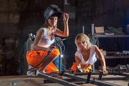 Brigade of two sexy welder women on the workshop background. Stock Photo
