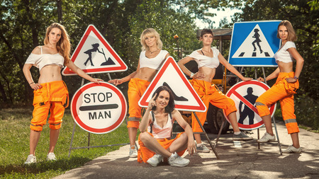 mounting: Five women in orange overalls are mounting  No Men signs on the road. Stock Photo