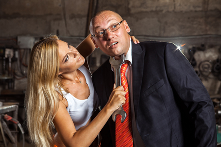 punishing: Blond woman is punishing his boss with the wrench. Workshop on the background. Stock Photo
