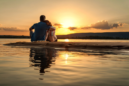 loving couples: Beautiful couple is sitting on the beach and looking at the sunset