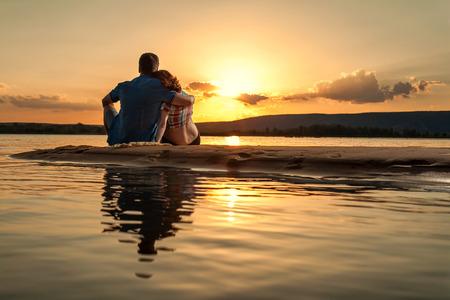 parejas enamoradas: Hermosa pareja está sentada en la playa y mirando a la puesta del sol