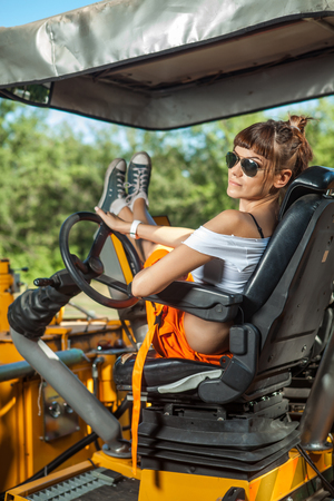 Sexy woman in orange overalls is operating the tractor.