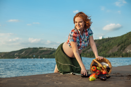 Pregnant red haired woman is picking up fruits into the basket on the beach. Stock Photo