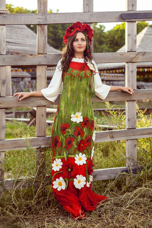 Young woman in Russian traditional dress is standing near wooden fence.
