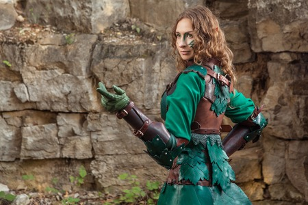 gesticulate: Elf woman in green leather armor pointing on something. Stock Photo