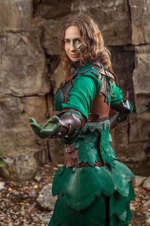 invitando: Elf mujer en la armadura de cuero verde le está invitando. Foto de archivo