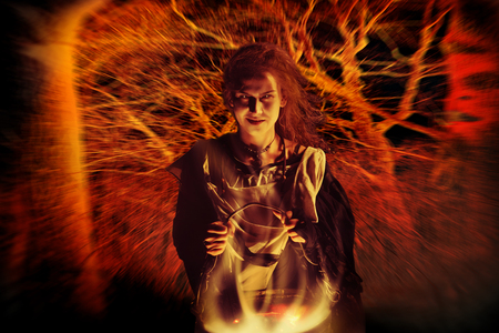 Pretty sorceress with the magic cauldron on the Bloody red forest background. Stock Photo
