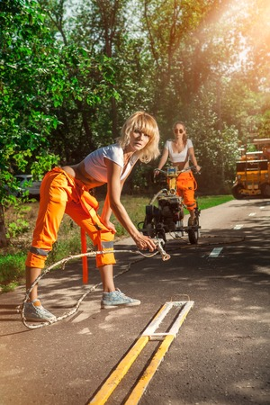 airbrush: Woman worker is drawing a road marking with the airbrush. Stock Photo
