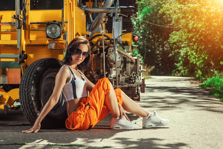 overol: Sexy woman worker in overalls is sitting near the tractor.
