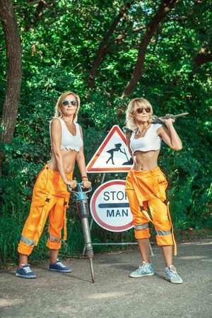 Two sexy women workers in overalls with the jackhammers.