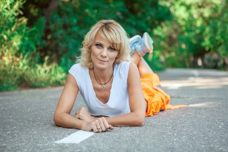 Sexy woman worker in overalls is laying on the road. Stock Photo