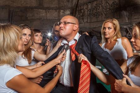 punishing: Women brigade is punishing their boss. Workshop on the background.