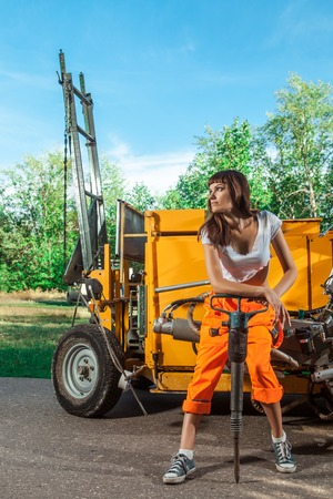 Sexy woman worker in overalls with the jackhammer. Stock Photo