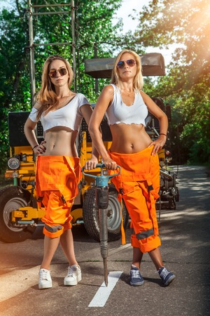 Two sexy women workers in overalls with the jackhammer. Stock Photo