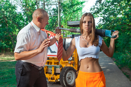 displeased businessman: Sexy woman worker in overalls with the jackhammer is holding boss tie. Stock Photo