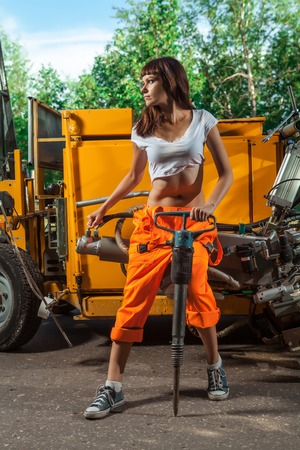 overalls: Sexy woman worker in overalls with the jackhammer. Stock Photo