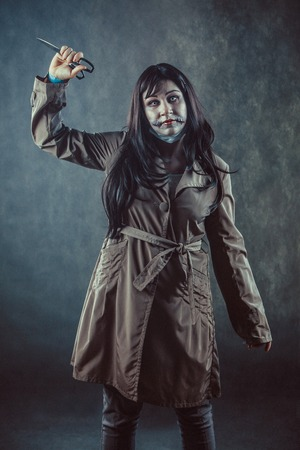 Zombie girl with the broken mouth with the scissors in a hand. Stock Photo