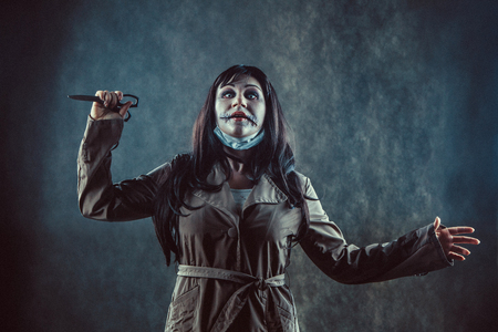 death head holding: Zombie girl with the broken mouth with the scissors in a hand. Stock Photo