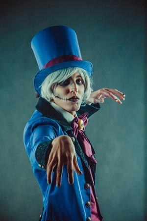 Sad gesticulating circus actor in blue tuxedo.