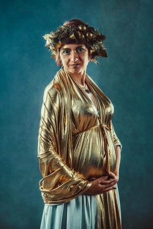 toga: Mujer embarazada en la toga de oro y una corona que presenta como una diosa de la fertilidad Grecia Demetra Foto de archivo