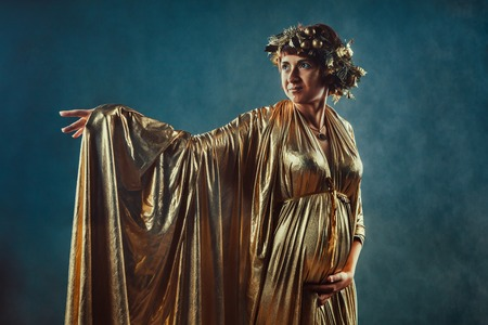 i i  i i toga: Mujer embarazada en la toga de oro y una corona que presenta como una diosa de la fertilidad Grecia Demetra Foto de archivo