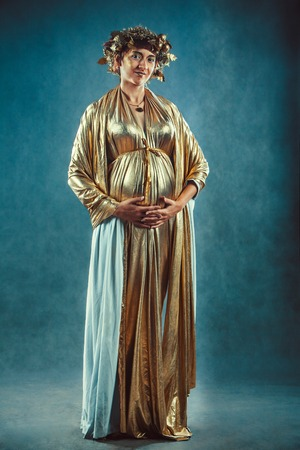 fertility goddess: Pregnant woman in golden toga and wreath posing like a Greece fertility goddess Demetra