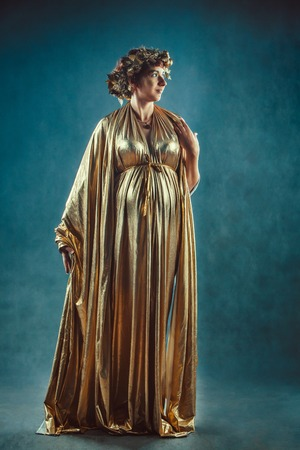 toga: Pregnant woman in golden toga and wreath posing like a Greece fertility goddess Demetra