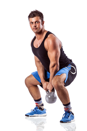 Sexy athletic man showing muscular body with weight, full length, isolated over white background.