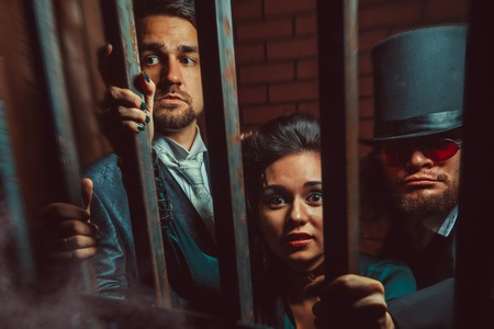 fatality: Two gentlemen and a lady behind bars in the prison.