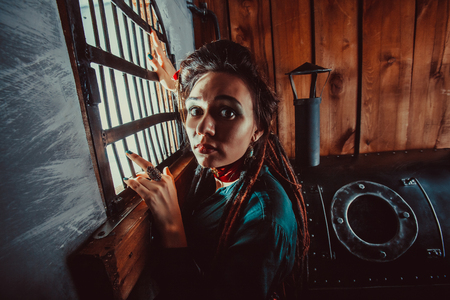 waiting convict: Sad lady near the window in the prison. Stock Photo