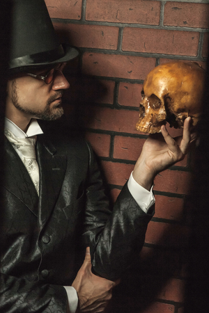 death head holding: Smart gentleman in cylinder hat and tie in the prison cage.