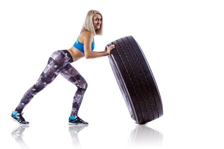 musculation: Young fitness woman execute exercise with large tire casing. Isolated over white background.