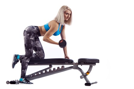 Woman in gym exercising with dumbbells lifting weights, working out on her biceps. Stock Photo