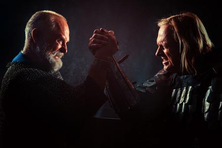 Medieval knights arm wrestlers on the dark background.