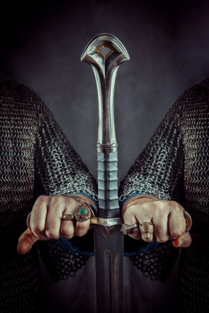 Two powerful knights are holding one sword. Archivio Fotografico