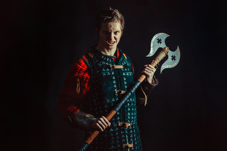 squire: Young medieval warrior with the axe. Dark background.