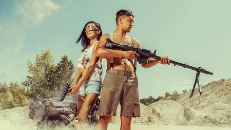Sexy couple of bikers with the guns on the desert background. Stock Photo