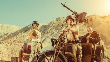 Military patrol of two powerful bald soldiers and woman on the desert background.