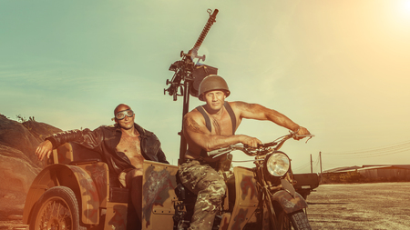 Two powerful bald soldiers with guns on the military tricycle. Stock Photo