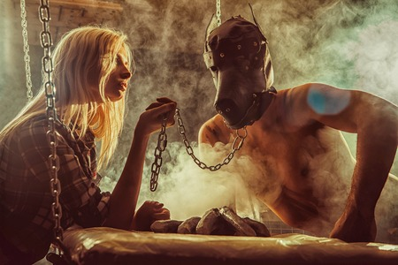 Young couple in a role playing game, girl is holding a man in the dog mask on the chain.