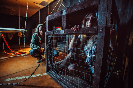 Bloody maniac and his female victim in the cage. Stock Photo