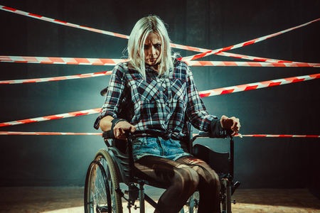 bounded: Pretty woman in the wheelchair on the dark background.