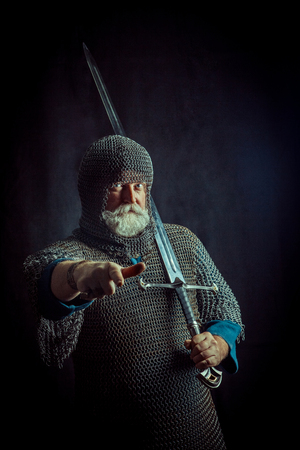 Powerful bearded knight with the sword on the dark background