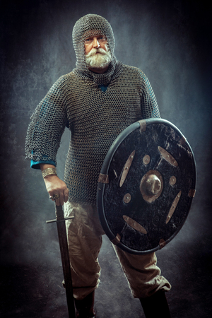 Powerful bearded knight with the sword and shield on the dark background