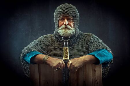 Powerful bearded knight with the dagger on the dark background