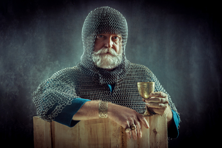 Powerful bearded knight with the glass of wine on the dark background.
