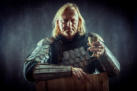 Powerful blond knight with the glass of wine on the dark background.