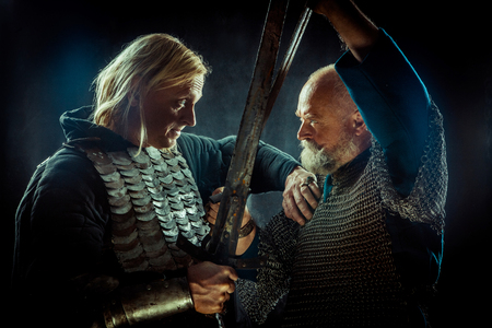 Medieval knights are fighting on swords. Dark background. Stock Photo