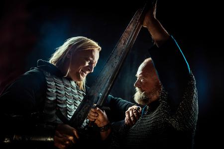 Medieval knights are fighting on swords. Dark background. Banco de Imagens