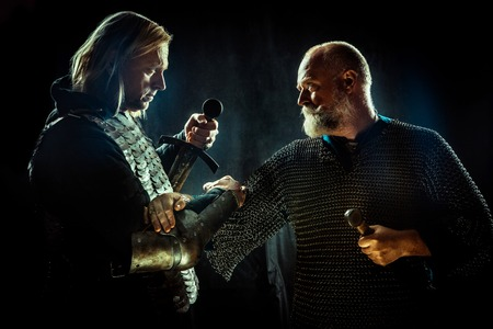 Medieval knights are crossing their hands in the brotherhood of War. Dark background. Stock fotó